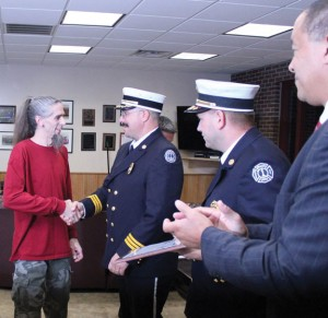 Tim Quinn of Beacon Falls, left, is congratulated by Beacon Hose Company No. 1 Assistant Fire Chief Ray Buzgo during a ceremony Monday night at the firehouse as Fire Chief Michael Pratt (second from right) and First Selectman Gerard Smith applaud. –ELIO GUGLIOTTI
