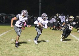 Naugatuck's Jason Bradley (13) and Nate Franklin (21) run an option as Woodland's Coby Vaccarelli (25) defends Oct. 4 in Beacon Falls. The Hawks won the game, 25-22. –ELIO GUGLIOTTI
