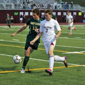 Naugatuck's Jason Szarzynski (3) jockeys with Austin Smith of Holy Cross for position as they chase down the ball Oct. 17 in Naugatuck. The Greyhounds won the game, 2-0, and capped a perfect regular season with a 1-0 victory over Wilby Monday night. –ELIO GUGLIOTTI