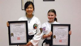 Sokol's Taekwondo students Hannah Kim, left, Kaia Lynn Schwartz, Maria Oliveira (not pictured) and Elijah Johnson (not pictured) were recently promoted to 1st Degree Black Belts. –CONTRIBUTED