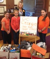 Naugatuck public schools and the Board of Education office participated in the GO ORANGE campaign Sept. 25 as part of No Kid Hungry Month. Students and staff showed their support by wearing orange clothing, tying orange ribbons on trees, decorating classrooms or doors in orange and holding food drives. Thousands of non-perishable food items were collected and donated to the Naugatuck Ecumenical Food Bank. Pictured: Salem Elementary School Principal Jennifer Kruge and students pose with food donations collected as part of the GO ORANGE campaign. –CONTRIBUTED