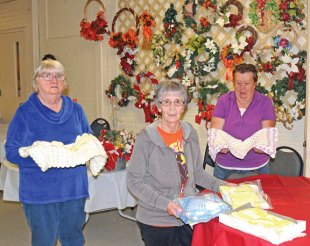 Josephine Fazzino, center, displays packages of baby blankets, hats and booties that she crocheted to sell at the Naugatuck Senior Center's annual Holiday Bazaar Tuesday at the center as Darlene Striffler, left, and June Ottowell hold a blanket made by Fazzino that will also be for sale. The bazaar will be held Nov. 2 at the senior center, 300 Meadow St.-LUKE MARSHALL