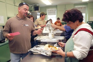 Volunteer Joe Leclerc has a plate order filled out by volunteer Mary MacInnis during the annual free Thanksgiving dinner in 2011 held at St. Michael's Church in Naugatuck. –RA ARCHIVE