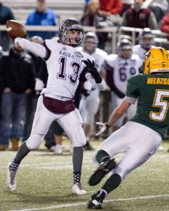 Naugatuck's Jason Bradley throws a touchdown pass to Bryan Coney against Holy Cross at Municipal Stadium in Waterbury Nov. 7 as the Crusader's Aaron Velasquez (5) rushes off the end. The Greyhounds topped the Crusaders, 56-20. –RA ARCHIVE