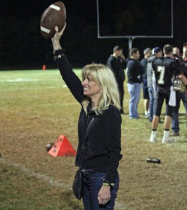 Jane Pinho holds the game ball up to the crowd following Woodland's win over Naugatuck Oct. 4 in the inaugural George Pinho Memorial Trophy game. –ELIO GUGLIOTTI