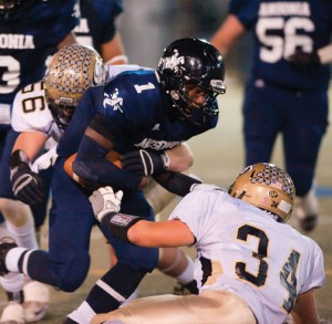 Ansonia's Jai'Quan McKnight (1) gets brought down by Woodland's Max McSperrin (56) and Chris Slavin (34) during the NVL championship game against Ansonia Nov. 20 at Municipal Stadium in Waterbury. Ansonia won the game, 48-7. –RA ARCHIVE