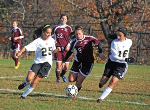 Woodland's Maribella Sousa (25) and Gillian Hotchkiss (16) close in on Windham's Jamey Martyn (9) Monday during the first round of the Class M tournament in Beacon Falls. Woodland won the game, 2-0. –LUKE MARSHALL