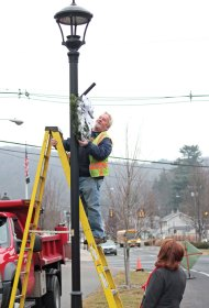 Mike Classey of the Beacon Falls Street Department hangs a wreath on a lamp post along the streetscape in downtown Beacon Falls Monday morning as Liz Falzone, co-chair of the Citizens for Tomorrow's Downtown, looks on. Rick Cherhoniak, co-chair of the group, is looking into the possibility of installing outlets on the lamp posts in order to add more holiday decorations in the future. This year, Falzone worked with designer Jenna Limosani of AC Moore in Orange to design the wreaths, which have been decorated with silver and cracked ice decorations. -ELIO GUGLIOTTI