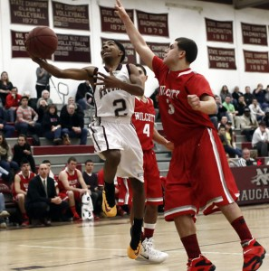 Naugatuck's Jordan Booker takes the ball to the hoop through Wolcott's Vin Gambino (4) and Jay Matos during Naugy's 63-38 win in Naugatuck Dec. 27. –RA ARCHIVE