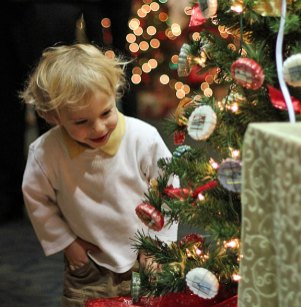 """Young Jack Mezzo, of Naugatuck, smiles as he checks out """"The Sweet Smells of Christmas"""" tree, donated by the Bennett family, during a reception to open the United Way of Naugatuck and Beacon Falls' 7th annual Festival of Trees Dec. 6 at Ion Bank on Church Street in Naugatuck. –ELIO GUGLIOTTI"""