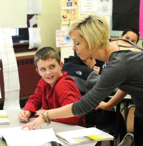 Hillside Intermediate School sixth-grade math teacher Karie Stango goes over an assignment with sixth-grader Mason Bedard Monday morning at the school in Naugatuck. Over the past four years, Hillside has risen from being labeled a failing school under the federal No Child Left Behind act to the top performing school in the district. –LUKE MARSHALL