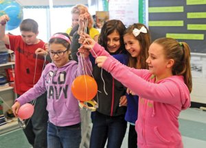 Cross Street Intermediate School fifth-graders, from left, Breanna Delagrange, Nicole Del Re, Alia Filandro and Emma Rocchio transport a balloon across their classroom using only strings attached to a roll of masking tape Feb. 4. –LUKE MARSHALL