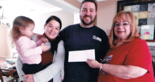 The Naugatuck Woman's Club has started a new medical fund that helps individuals defray medical expenses. So far, the fund has awarded five recipients. Pictured, club treasurer Beverly Hudson, right, presents a check to the family of 2-year-old Abbey Denley, who has cancer. -CONTRIBUTED