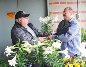 Naugatuck firefighter Sean Reilly, right, shows retired Naugatuck Fire Department dispatcher Vidas Melninkaitis a flower during the department's annual Easter flower sale April 19. The money raised from the sale goes to help nonprofit organizations. –LUKE MARSHALL