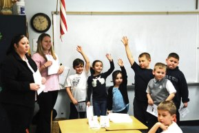 Naugatuck Valley Savings and Loan employees Jessica Gonzalez, left, and Caitlin McAllister teach first graders at St. Francis-St. Hedwig School in Naugatuck about where is the safest place to keep their money on April 11. Gonzalez and McAllister were at the school as part of the Teach Children to Save Campaign. Throughout the week students in grades kindergarten through eight were taught the best ways to save their money for the future. –LUKE MARSHALL