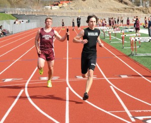 Woodland's Tom Bethin, right, finishes the 4-by-100 relay just ahead of Naugatuck's Adam Branco to give the Hawks' the win in the event April 22 at Naugatuck. The Woodland boys and girls both picked up victories over Naugatuck. –LUKE MARSHALL