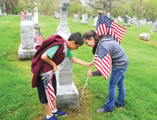 City Hill Middle School seventh-graders Andres Maldonado, left, and Shannon Burns place a flag on the grave of a veteran at St. James Cemetery in Naugatuck May 15. City Hill students assisted brothers Bill and Manny Matos to put flags on the graves of veterans in preparation for Memorial Day. The Matos brothers, who are both veterans, have been putting flags on the graves for 20 years. Bill Matos, who used to work as a custodian at City Hill, has enlisted the help of students for many years. Maldonado enjoyed being given the opportunity to place the flags. 'It feels like I am doing something great. It's for the veterans,' Maldonado said. –LUKE MARSHALL