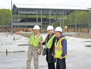 From left, Region 16 Board of Education member Robert Hiscox, interim Superintendent of Schools Gail Gilmore and project engineer Phil Mazzatti, from Turner Construction Company, check out construction of the new Prospect Elementary School on New Haven Road in Prospect May 23. The three are standing on the foundation of what will be a two-story wing for classrooms. Behind them, the gymnasium is taking shape. –ELIO GUGLIOTTI