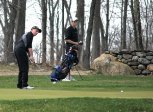 Woodland's Ryan Warner putts on the first green as teammate Andy O'Dell watches April 28 at Oxford Greens in Oxford. Woodland faced Naugatuck on the links and the Hawks earned a 198-205 victory. –ELIO GUGLIOTTI