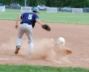 Naugatuck's Jason Bradley dives back to first base in a cloud of dirt Tuesday versus Ansonia in the quarterfinals of the NVL tournament at Rotary Field in Naugatuck. The Chargers knocked out Naugatuck, 3-2. –KEN MORSE