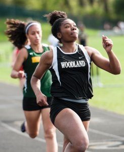 Woodland's Ashley Michie wins the 100 meter dash Tuesday in Beacon Falls ahead of Holy Cross' Keili Sullivan. The Woodland boys and girls teams beat Holy Cross, St. Paul and Derby to claim the NVL titles. –RA ARCHIVE