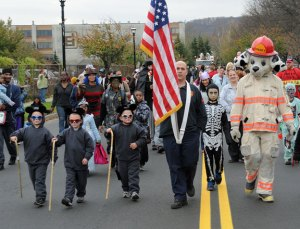 Lt. John Debisschop of the Naugatuck Fire Department leads the annual Halloween parade in 2012 with his triplet sons (dressed as the Three Blind Mice) Jeffrey, John and Jack. Debisschop is among several borough firefighters who have twins or triplets. –FILE PHOTO