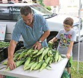 Tom Giammattei, left, and his son Wyatt Giammattei of The Flower Farm in Prospect stack ears of corn July 9 during opening day of the Naugatuck farmers market on the Town Green. Giammattei said sales were a bit slow, but that was to be expected on the first day. 'It's always slow in the beginning until people know you're here. Then it will pick up,' Giammattei said. Marcucio Farms and Greenhouses of Ansonia was also on hand for the first day. The farmers market is open Sundays from 9 a.m. to 1 p.m. and Wednesdays from 10 a.m. to 2 p.m. –LUKE MARSHALL