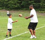 Brayden Curtin of Prospect tosses a football to former NFL quarterback Daunte Culpepper during the Bags All-Star Football Camp hosted by the Woodland Jr. Hawks July 19 at Caplan Park in Prospect. Culpepper, who played 11 seasons in the NFL, worked with campers on proper stances and on how to throw a pass. –LUKE MARSHALL