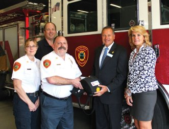 From left, Naugatuck Deputy Chief Ellen Murray, Firefighter Stephen Hebb, Fire Chief Kenneth Hanks, Ion Bank President and CEO Charles Boulier III, and Deputy Mayor Tamath Rossi pose for a picture with the fire department's new Automated External Defibrillator or AED. The department bought the AED with a $1,695 grant from the Ion Bank Foundation. The new AED unit, which was ordered when the department received the grant in February, arrived in August and was placed on Engine 3, which runs out of the department's eastside station. Defibrillators are electronic devices that can give an electrical shock to the heart of victims who are undergoing cardiac-related emergencies. 'This is the first time such a piece of equipment has been put into service on an emergency vehicle in the Naugatuck Fire Department,' Murray wrote in a thank you letter to the Boulier. –CONTRIBUTED