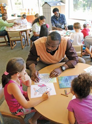 Former NFL tight end and current motivational speaker Benjamin Troupe compares his coloring with Kayla Kelly, 9, of Naugatuck at the Whittemore Library Aug. 14. Troupe was at the library along with professor Kelly Downing and author Corey Parks as part of Success is a Journey, a program the provides motivational speaking and advocates for academic and social change. -LUKE MARSHALL