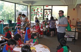 Whittemore Library Children's Librarian Matthew Yanarella helps children create superheroes at the Whittemore Library in Naugatuck July 23. The library handed out capes and masks for the children to wear as part of Superhero Week. The weeklong celebration, which was in honor of the 75th anniversary of the creation of Batman, included a superhero parade and screening of the 1966 Batman: The Movie. –LUKE MARSHALL