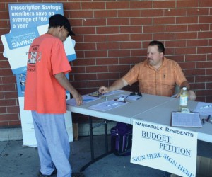 Matt Katra tells a resident where to sign on a petition sheet that Katra and others will use to force a referendum on the proposed budget. Katra has been a driving force behind the petition drive. –RA ARCHIVE