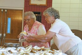 Naugatuck residents Flora Fidalgo, right, and Caroline Pereira frost cavacas cookies at the Naugatuck Portuguese Club last year in preparation for the annual Feast of Sao Paio. The festival runs Sept. 4 through Sept 6 this year. –FILE PHOTO