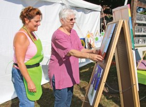 Lori Maynard, left, and Rose-Ann Chrzanowski, of BrushStroke Paint Party in Naugatuck, set up paintings in 2015 during the annual Harvest Moon Festival on the Naugatuck Green. -FILE PHOTO