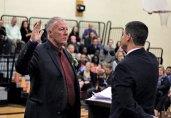 Naugatuck Mayor N. Warren 'Pete' Hess, left, is sworn in for his first term in office Nov. 17 by outgoing Mayor Robert Mezzo at Hillside Intermediate School. –ELIO GUGLIOTTI