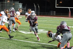 Naugatuck's Antoine Sistrunk (1) picks up of some of his 238 yards on the ground with the help of a block by Etty Ilunga (2) during the Greyhounds' 40-23 win over Watertown in Naugatuck Oct. 29. –ELIO GUGLIOTTI