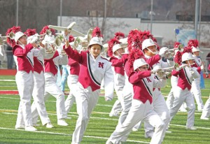 The Naugatuck High School marching band and color guard perform at halftime of the Thanksgiving Day football game. –FILE PHOTO