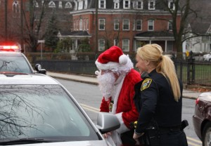 Naugatuck police detectives Paul Markette, dressed as Santa, and Amanda Devan talk with Naugatuck resident Andrew Karistinos after pulling him over on Church Street Christmas Eve and giving him a gift card to Dunkin' Donuts. –LUKE MARSHALL