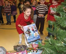 Maple Hill Elementary School kindergartner Mia Orsini puts a present under a Christmas tree at the school in Naugatuck Dec. 22 during a holiday celebration. Students at the school donated presents, which were collected and distributed to families in need by members of the Naugatuck Fire Department. In addition to the toy drive, the celebration also included holiday songs and a visit from Santa Claus. –LUKE MARSHALL