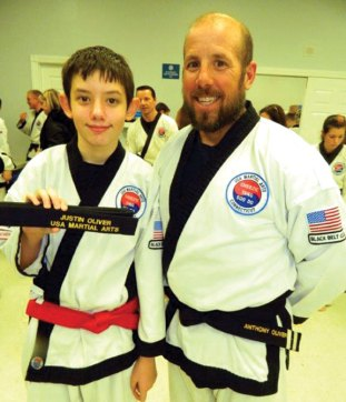 Justin Oliver, left, from USA Martial Arts in Naugatuck was promoted to 1st Black Belt in Cheezic Tang Soo Do Karate Feb 19. Oliver is pictured with his father, 2nd Dan Black belt Anthony Oliver. –CONTRIBUTED