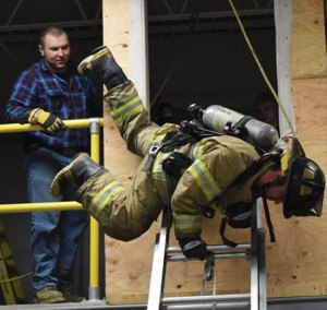 Beacon Hose Company No. 1 Firefighter Adam Daniels trains using a second-floor window prop as Firefighter Cal Brennan looks on during a recent training exercise at Station 2 on Railroad Avenue in Beacon Falls. Members of the department have built training props to use at the station. –BEACON HOSE