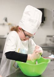 Salem Elementary School fourth-grader Aubrey Longanecker mashes bananas for her scrambled French toastlesss recipe during the Sodexo Future Chef competition March 9 at Naugatuck High School.–ELIO GUGLIOTTI