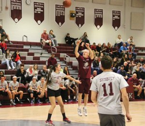 Naugatuck High School teacher and DECA adviser Tim Reilly shoots over sophomore Molly Kennedy March 24 during the Clash for the Cure basketball game. –LUKE MARSHALL