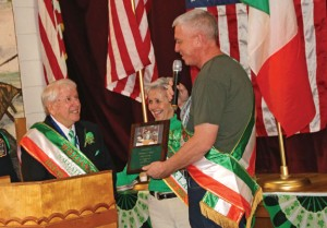 Naugatuck's Irish Mayor of the Day William Ward, left, is presented with a plaque by President of the Naugatuck Ladies Ancient Order of Hibernians Mary Ann Skehan Sigworth, center, and President of the Naugatuck Ancient Order of Hibernians James Goggin March 17 during a ceremony at the Naugatuck Portuguese Club. –LUKE MARSHALL