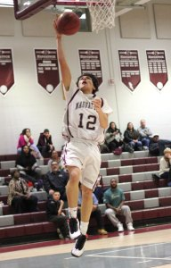 Naugatuck's Andre Trosan (12) finishes off a fast break with a layup versus Woodland Feb. 25 in Naugatuck. Naugatuck won the game, 63-26. –ELIO GUGLIOTTI