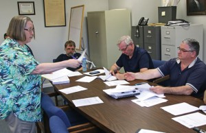 Beacon Falls Library Director Sue Dowdell, left, hands out emails from residents supporting the library to members of the Board of Finance May 12 during a public hearing on the budget at Town Hall. The town's $6.37 million municipal will go to a town meeting for a vote on May 26. –LUKE MARSHALL