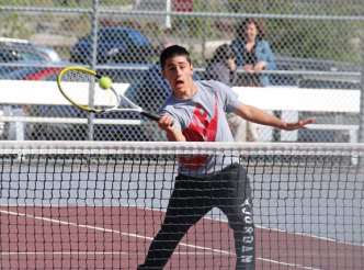 Naugatuck's Jared Montini returns a shot against Sacred Heart's Brennan Sanders during the first round of the NVL tournament Monday at Naugatuck High School. Naugatuck won the match, 5-1. –LUKE MARSHALL