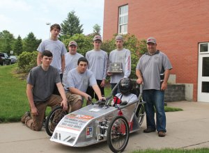The Woodland Regional High School team won first place in the novice division at the Connecticut Electrathon. Pictured, kneeling from left, Alec Richards, Albert Herb; standing from left, Hayden Bartlett, Tim Deschaenes, Tom Lawlor, Drew Korzon, teacher Bill Carangelo; in the car, Jordan Baer. –ELIO GUGLIOTTI