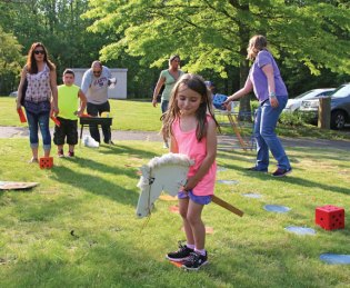 Maple Hill Elementary School kindergartner Melissa Paternoster rides a fake horse during the school's Family Math Carnival on May 25. The event was the culmination of the school's monthly math activity nights. Students were treated to a wide variety of math games, cotton candy, and prizes. –LUKE MARSHALL