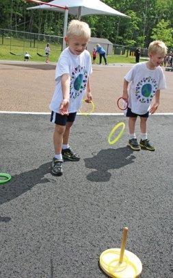 Prospect Elementary School kindergartners River McGeehan, left, and Dustin Guertia play a ring toss game during Field Day at Prospect Elementary School June 9. –LUKE MARSHALL